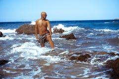 Красивый молодой парень в голубом море стоковое фото
