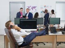 Красивый молодой парень в костюме говоря на мобильном телефоне, сидя в офисе с ногами на настольном компьютере Стоковое Изображение