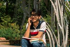 Красивый молодой парень держит книги и звенеть стоковые фото