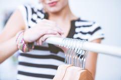 Красивый молодой стилизатор около шкафа с вешалками в офисе стоковое изображение rf