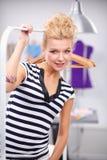 Красивый молодой стилизатор около шкафа с вешалками в офисе стоковая фотография rf