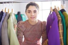 Красивый молодой стилизатор около шкафа с вешалками стоковые изображения