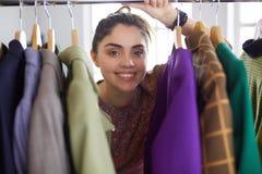 Красивый молодой стилизатор около шкафа с вешалками стоковые фотографии rf