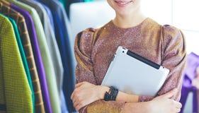 Красивый молодой стилизатор около шкафа с вешалками стоковое фото