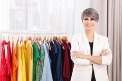 Красивый молодой стилизатор около шкафа с дизайнерской одеждой стоковые фотографии rf