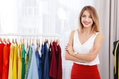 Красивый молодой стилизатор около шкафа с дизайнерской одеждой стоковое фото rf