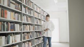 Красивый молодой студент идя между книжной полка с книгой в руках сток-видео