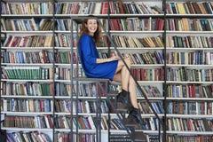 Красивый молодой студент колледжа сидя на лестницах в библиотеке, работая на компьтер-книжке Женщина нося голубое платье, огромны стоковая фотография