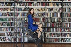 Красивый молодой студент колледжа сидя на лестницах в библиотеке, работая на компьтер-книжке стоковое изображение rf