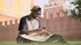 Красивый молодой турист сидя с картой около красной площади в Москве акции видеоматериалы