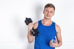 Красивый молодой человек в голубой рубашке держа гантель и бутылку с водой o стоковое фото