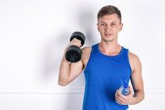 Красивый молодой человек в голубой рубашке держа гантель и бутылку с водой o стоковое изображение rf
