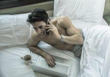 Красивый молодой человек в кровати вызывая на сотовом телефоне Стоковое Изображение