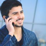Красивый молодой человек в простых одеждах, говоря телефон Стоковые Фото