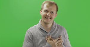 Красивый молодой человек в сером свитере делая жест любов o видеоматериал