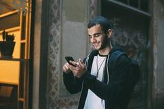 Красивый молодой человек использует телефон стоковое изображение rf