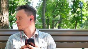 Красивый молодой человек носит красные наушники музыки акции видеоматериалы