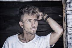 Красивый молодой человек против деревянной стены планок Стоковые Изображения