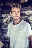 Красивый молодой человек против деревянной стены планок Стоковое Фото