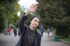 Красивый молодой человек развевая к кто-то, идущ, улица стоковое фото rf