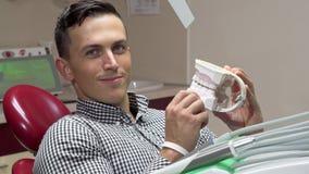 Красивый молодой человек рассматривая зубоврачебную прессформу, усмехаясь к камере сток-видео