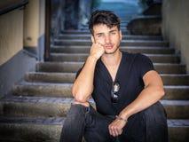 Красивый молодой человек сидя в европейском переулке города Стоковые Изображения