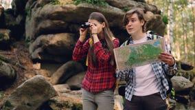 Красивый молодой человек смотрит карту пока его друг наблюдает в биноклях, указывая на интересное место и акции видеоматериалы