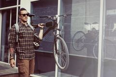 Красивый молодой человек с рюкзаком носит велосипед на его концепции Livestyle плеча ежедневной по заведенному порядку стоковые фото