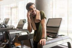 Красивый молодой человек усмехаясь пока говорящ на мобильном телефоне во время Стоковые Фотографии RF