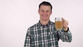 Красивый молодой человек усмехаясь joyfully, держащ вне его пиво к камере видеоматериал