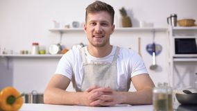 Красивый молодой шеф-повар усмехаясь в камеру, объявление кулинарных курсов, подсказок питания сток-видео