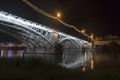 Красивый мост Triana рядом с рекой Гвадалквивира на своем пути через город Севильи, Андалусии Стоковое Фото