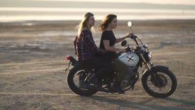 Красивый мотоциклист молодой женщины при его подруга ехать мотоцикл в пустыне на заходе солнца или восходе солнца Женщина 2 на ве видеоматериал