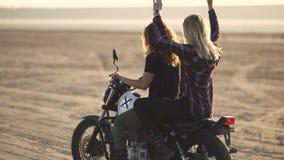 Красивый мотоциклист молодой женщины при его подруга ехать мотоцикл в пустыне на заходе солнца или восходе солнца Танцы 2 женщин  видеоматериал