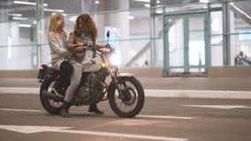 Красивый мотоциклист молодой женщины при его подруга ехать мотоцикл в городе ночи на освещенной улице Женщина 2 на велосипеде видеоматериал