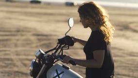 Красивый мотоциклист молодой женщины при его подруга ехать мотоцикл в пустыне на заходе солнца или восходе солнца Подруги на вело сток-видео