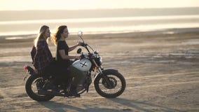 Красивый мотоциклист молодой женщины при его подруга ехать мотоцикл в пустыне на заходе солнца или восходе солнца Подруги на вело акции видеоматериалы