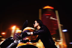 Красивый мотоцикл катания молодой женщины в солнечных очках через улицы города на ноче Стоковое фото RF