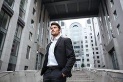 Красивый молодой бизнесмен в костюме стоя близко деловый центр Стоковое Изображение