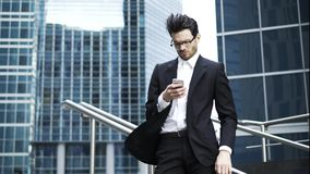 Красивый молодой бизнесмен в стеклах отправляя СМС outdoors в ветре видеоматериал
