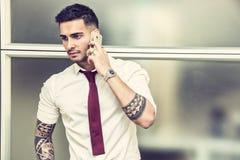 Красивый молодой бизнесмен говоря на сотовом телефоне Стоковая Фотография RF