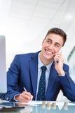 Красивый молодой бизнесмен говоря на умном телефоне в офисе Стоковые Фото