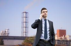 Красивый молодой бизнесмен на предпосылке промышленного здания Стоковая Фотография
