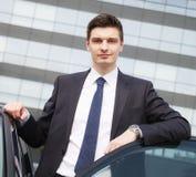 Красивый молодой бизнесмен около его автомобиля Стоковое фото RF