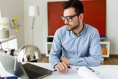 Красивый молодой бизнесмен работая с компьтер-книжкой в офисе Стоковые Фотографии RF