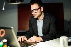 Красивый молодой бизнесмен работая с компьтер-книжкой в офисе Стоковая Фотография