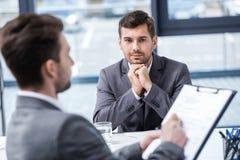 Красивый молодой бизнесмен смотря менеджера с доской сзажимом для бумаги на собеседовании для приема на работу Стоковые Фото