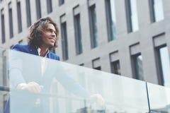 Красивый молодой бизнесмен стоя в городе смотря счастливый и удовлетворенный Стоковое Фото