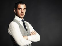 Красивый молодой бизнесмен стоя на черноте стоковая фотография