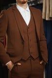 Красивый молодой бородатый бизнесмен в классическом костюме Человек носит куртку Оно в выставочном зале, пробующ на одеждах, пред Стоковая Фотография RF